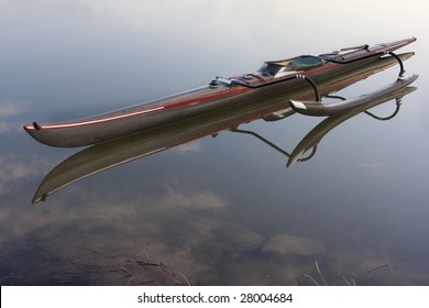 long and slim racing outrigger canoe (black carbon fiber design) with a compass and paddle on deck