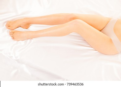 Long and slim woman legs on white sheets in bed