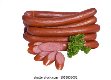 Long smoked sausages in a natural shell. Meat product decorated with branch of parsley. Isolated on white background