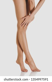 Long smooth woman legs standing on isolated on white background.