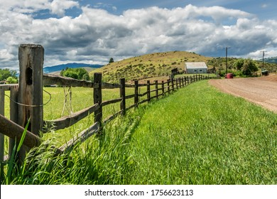 Long Split Rail Fence along a grassy field near a dirt roat leading up to a metal barn under the cloudy sky