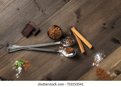 Long spoons on dark wood, cocoa and chocolate composition, aerial view