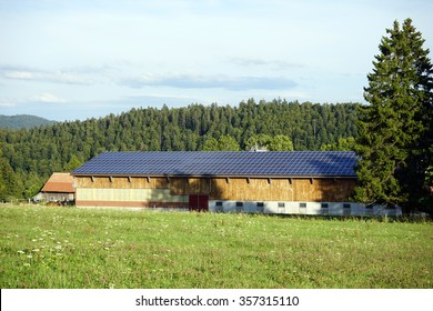Long stable with solar panel on the roof and farm field in Switzerland