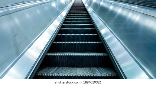 Long and steep escalators from the bottom looking upwards as a person is about to travel from the ground level up to the next floor. - Shutterstock ID 1894019326