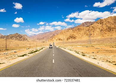 Long straight asphalt road leading towards to the great mountain and clouds on blue sky in summer day in Leh Ladakh, Jammu and Kashmir, India.