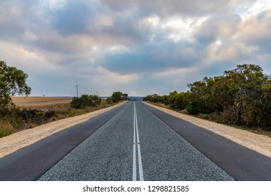Long straight Australian road with now cars and colorful clouds in Western Australia