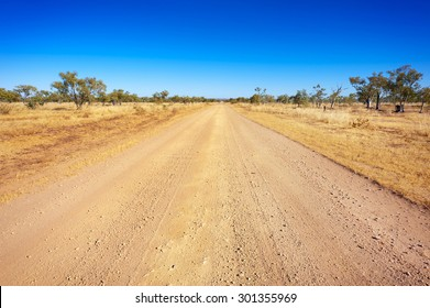 A long, straight dirt road disappears into the distant horizon.