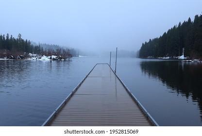 long straight dock on frigid foggy lake in winter