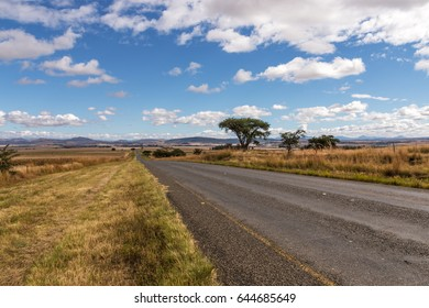 Long straight empty rural asphalt road running through dry winter mountain landscape against blue cloud sky horizon n Orange Free State in South Africa