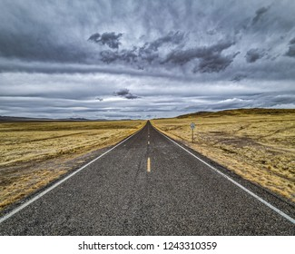 Long straight empty two lane desert highway near Great Salt Lake lakeside in Utah west desert near Tooele and Dugway on an overcast cloudy barren summer afternoon