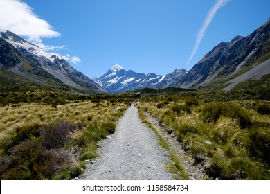 A long straight gravel road that leads to the famous breathtaking snow mountain in Mount Cook, New Zealand. The landscape is epic. There are snow mountain, glacier, alpine, rivers and valley.