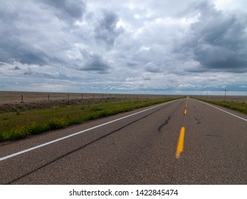 Long, straight prairie hiway with grasslands on either side and storm filled skies.