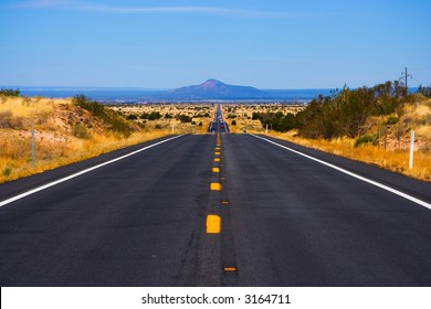 Long straight road with mountain on horizon