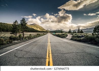 A long straight road in the nature towards snowy mountains in June Lake Junction, California with cracked asphalt and deep blue sky.