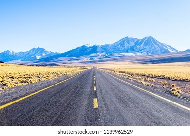 A long straight road that crosses the Atacama desert. Road to highlands lagoons. Lagunas altiplanicas, Chile, South America.