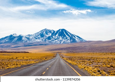 A long straight road with yellow and blue landscape that crosses the Atacama desert. In the region of the highlands lagoons. Altiplano Andino Atacama. July, 12 2018.