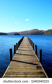 Long straight symetrical beautiful wooden foot jetty jutting out over a calm blue lake, with hills of green fields and forest woodland in the background, the sun is shining with a blue sky