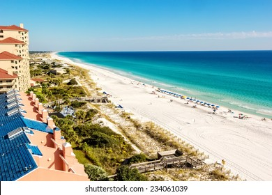 Long stretch of Miramar Beach, in Destin, Florida and the emerald green waters of the Gulf of Mexico.