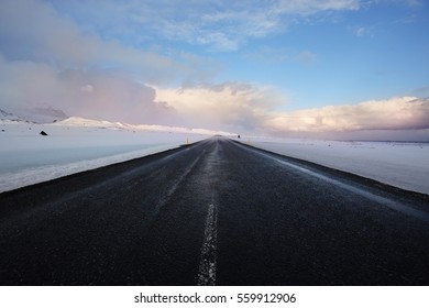 Long stretch of road through winter landscape