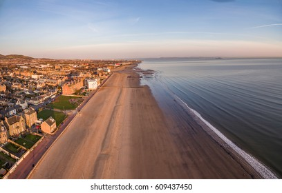 The long stretch of sandy beach of Portobello, Edinburgh's seaside viewed from the air. Scotland, United Kingdom