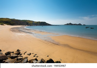 A long stretch of an untouched sandy crescent beach and distant headlands on Dongju Island on a clear sunny, blue sky day in the Matsu Islands of Taiwan. Horizontal copy space
