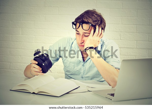 Long studying hours sleep deprivation concept. Tired sleepy young man sitting at desk with book in front of laptop computer looking at alarm clock