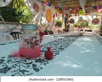 long table inside a temporary structure for Sukkot A Sukkah decorated  for holiday in Israel Green vegetation in the windows and on the table a pomegranate fruit With colored paper decorations