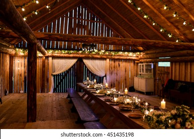 Long table stands in the wooden storage decorated for a wedding