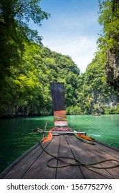 A long tail boat enters a secluded lagoon in Phang Nga Bay, Thailand