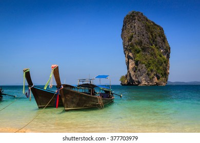 Long tail boat on the beautiful beach and beauty blue sky , poda