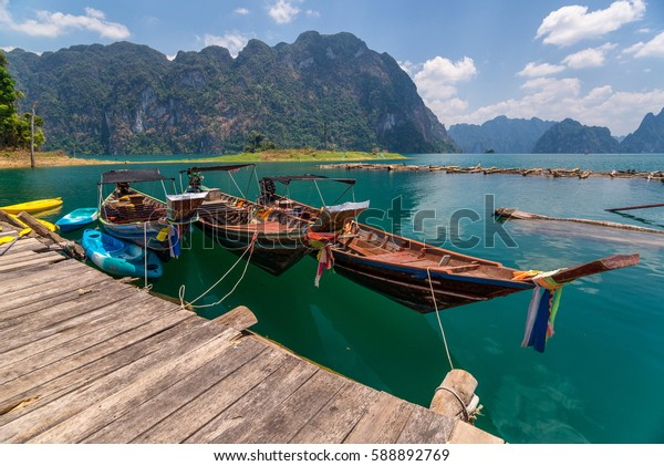 long tail boat on floating bamboo raft with beautiful lake and mountain background in the morning at ratchaprapa dam , khao sok national park in surat thani southern of thailand