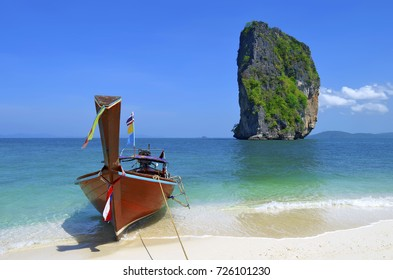 Long tail boat on Poda island beach with the famous Ko Ma Tang Ming rock, in the Andaman Sea, off Ao Nang beach, province of krabi, Thailand