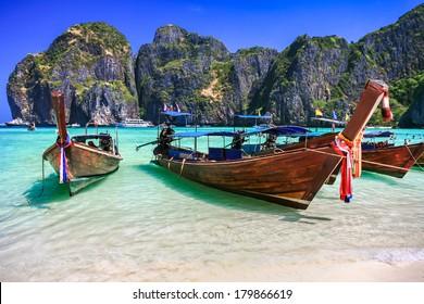 Long tail boat on white sand beach with crystal clear sea, Maya island, Krabi, Thailand
