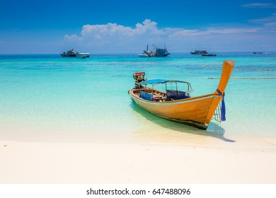 Long tail boat waiting for tourist in clear sky and white sand beach it a beautiful andaman sea with blue sky in a nice weather holiday at  Koh Li-pe, Sa-tun, Thailand