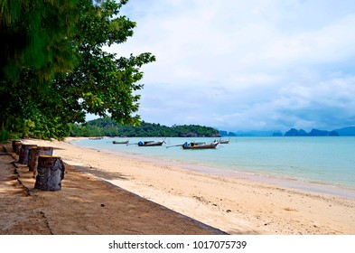 Long tail boats mooring at the Pa Sai beach on Koh Yao Noi with the Phang Nga Bay in the background, in the Andaman Sea, Thailand