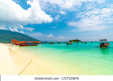 Long tail boats in small harbor at Ko Lipe island, south Thailand. Tropic and exotic island is symbol of tropical paradise, part of Tarutao national nature park. Vibrant colors, turquoise water.