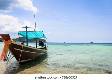 Long tail wood boat with flowers on prow at shore on calm sea in the island of Ko Pha Ngan, Thailand