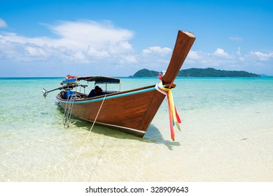 Long tail wooden boat anchor with csytal sea white sand at lipe island,andaman,thailand