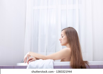 Long tangled brittle hair care and combing. Young pretty woman relaxes in bathtub with soap foam. Spa procedures in bathroom at home or hotelroom. Skin care and moisturizing for youth preservation.