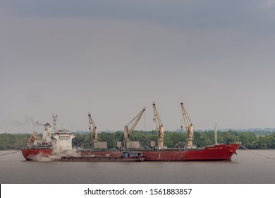 Long Tau River, Vietnam - March 12, 2019: Big red sea cargo vessel, Vissai VCT 05, with its own cranes anchored in brown water. Small river barge, along side, is loaded off the big ship. Green belt an