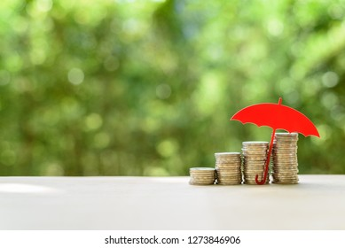 Long term money investment and wealth management with risk protection, financial concept : Red umbrella protects coins or cash on a table, depicts securing asset for sustainable growth for the future