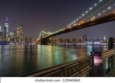 Long time exposure of New York City Manhattan downtown skyline and Brooklyn Bridge  at night viewed from Brooklyn Bridge park