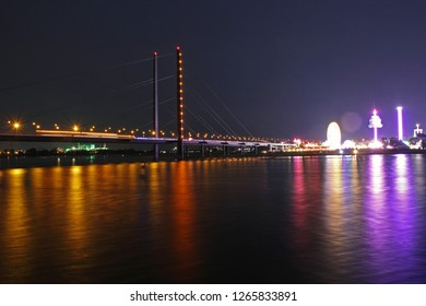 long time exposure of the rhine bridge with colorful lights of the funfair