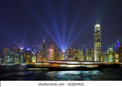 Long time exposure of ships floating in Hong Kong Harbour. Lasers and light beams on the Skyline are part of the  Symphony of lights show.