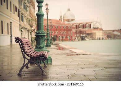 long time exposure of typical wooden bench on promenade in Venice (Venezia) on a rainy day in autumn without people, Italy, Europe, vintage filtered style