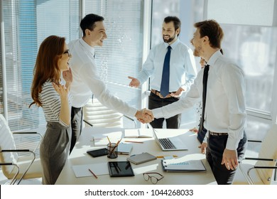Long time no see. Cheerful pleasant colleagues shaking hands with each other and exchanging smiles before starting the business meeting