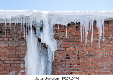 Long transparent icicles hang from the roof. The icy gutter is like a giant icicle. Icicles falling danger concept.