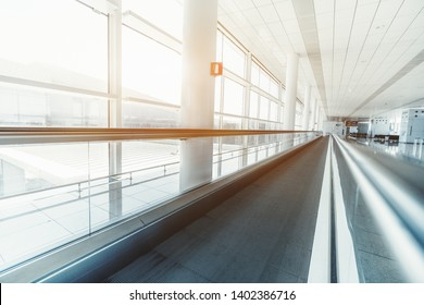 A long travelator in the interior of an airport terminal with huge windows on the left; wide-angle view of the moving walkway indoors of a railway station depot stretching into the distance