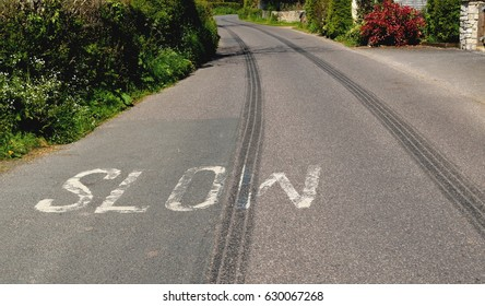 Long tyre track on the road with written sign SLOW