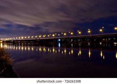 Long viaduct over water. Nice reflection of lights. Long exposure clouds.